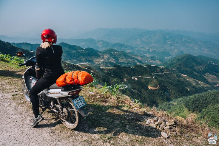 girl on a motorbike admiring a beautiful mountain landscape on Ha Giang Loop